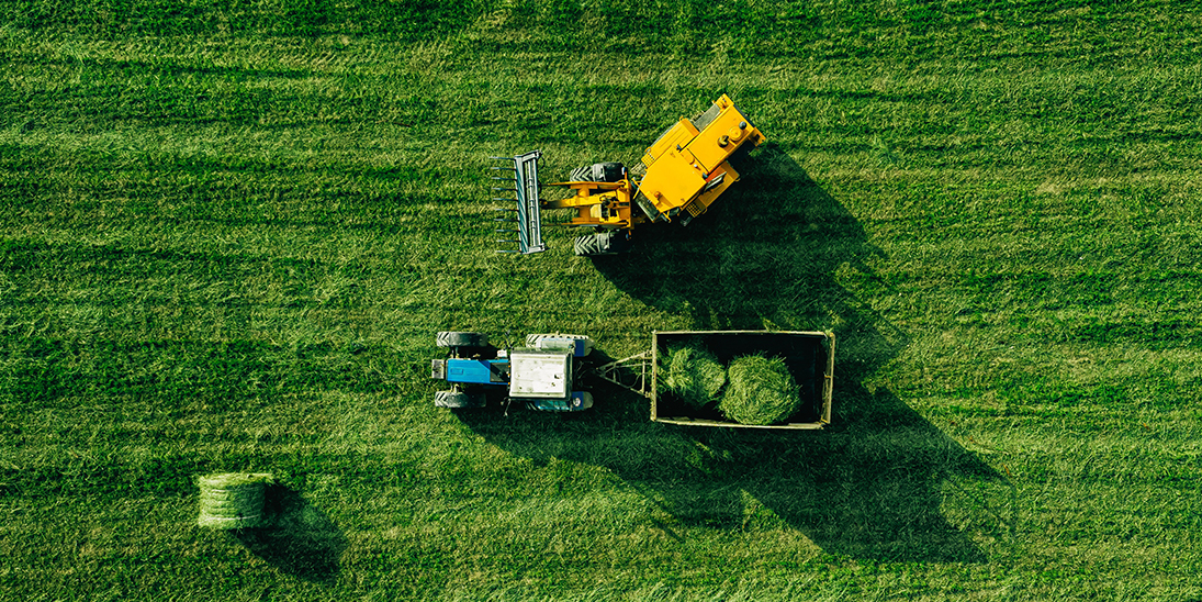 aerial view of harvest field with tractor moving