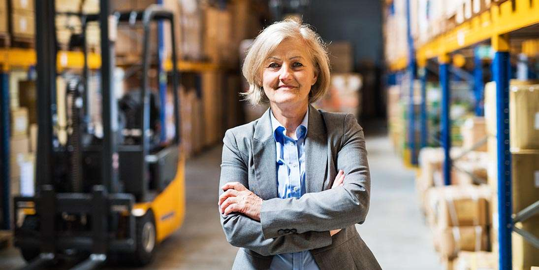 senior woman warehouse manager or supervisor arms